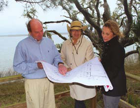 Client, architect and builder review floor plans for a proposed home